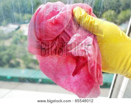 Hand In Yellow Glove Cleaning Window Glass