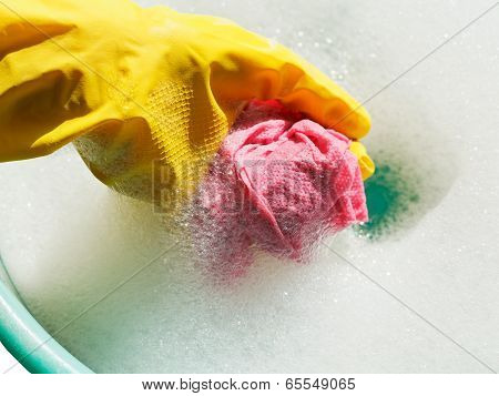 Hand In Yellow Rubber Glove Rinsing Rag