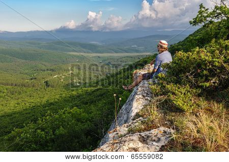 Young hiking man in the rays of sunset, standing at the top of Tope Kermen, Crimea, Ukraine or Russia