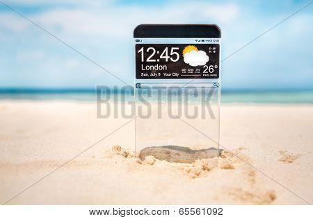 Futuristic Smart phone (copy space display) with a transparent display in the sand on the beach. Concept actual future innovative ideas and best technologies humanity.