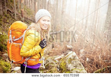Woman Hiking In Autumn Forest Trail