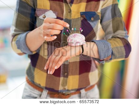 Closeup On Seamstress Putting Needle Into Pincushion
