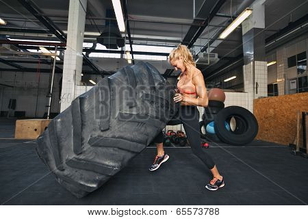 Young Woman Flipping Tire At Gym