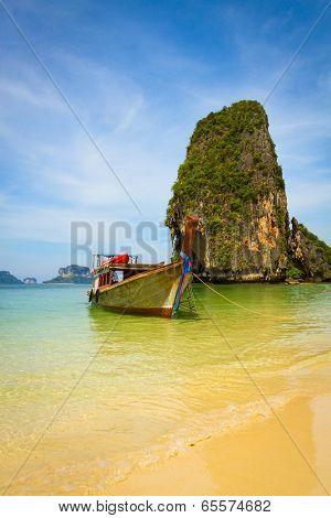Traditional thai longtail boat landing on sea coast. Krabi, Andaman Sea, Thailand