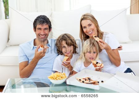 Smiling Family Eating A Pizza Sitting On The Floor