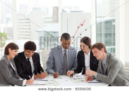 Concentrated Manager And His Team Studying A Document