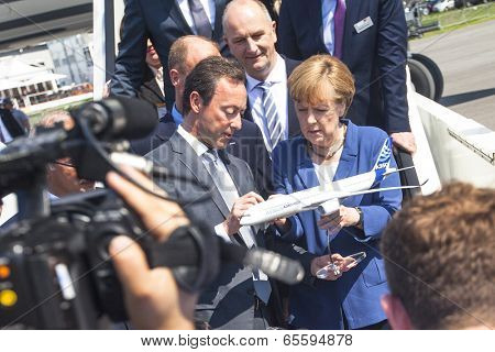 BERLIN, GERMANY - MAY 20, 2014: German Chancellor Angela Merkel look model airplane Airbus A350 XWB during open up the International aviation and space exhibition ILA.