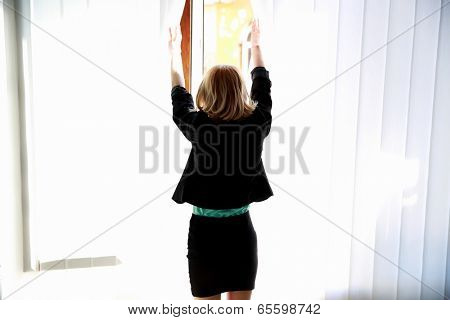 Back view portrait of a young woman looking at window
