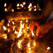 picture of hindu temple  - People burning oil lamps as religious ritual in Hindu temple - JPG