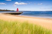 stock photo of tyne  - The Groyne Lighthouse at South Shields sits in the mouth of the River Tyne to protect the beach and help with navigation - JPG