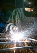 image of welding  - man welding with reflection of sparks on visor - JPG