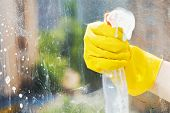 stock photo of window washing  - hand in rubber glove washes home window from spray bottle - JPG