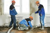 image of floor covering  - Plasterer workers at indoor concrete cement floor topping with float - JPG