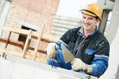 pic of bricklayer  - Portrait of construction mason worker bricklayer installing brick with trowel putty knife outdoors - JPG