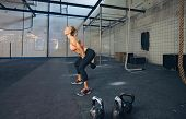 stock photo of kettling  - Young fitness female exercise with kettle bell. Caucasian woman doing crossfit workout at gym.