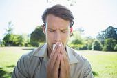 stock photo of hay fever  - Stylish man blowing his nose in the park on a sunny day - JPG