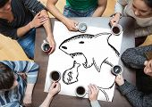 stock photo of loan-shark  - People sitting around table drinking coffee with page showing loan shark doodle - JPG