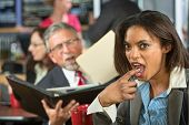 stock photo of gag  - Disgusted business woman gagging while man reads to her - JPG