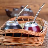 stock photo of calabash  - Yerba mate and mate in calabash on a wicker tray selective focus - JPG