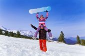 stock photo of snowboarding  - Happy snowboarder with young woman sitting on his shoulders who is holding snowboard over her head - JPG