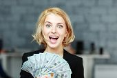 picture of holding money  - Young businesswoman holding money with delight - JPG