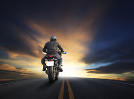 stock photo of biker  - young man riding big bike motocycle on asphalt high way against beautiful dusky sky use for biker traveling and journey theme