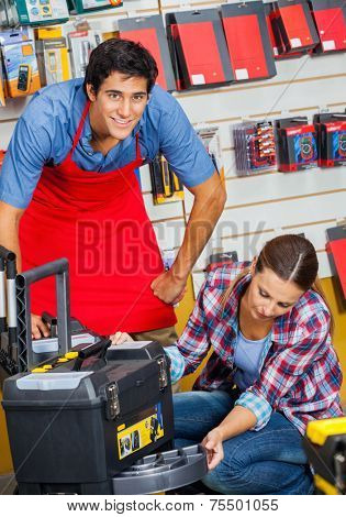 Portrait of smiling salesman with female customer examining tool case in hardware store