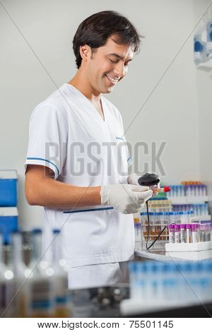 Happy young male technician scanning barcode on test tube in laboratory