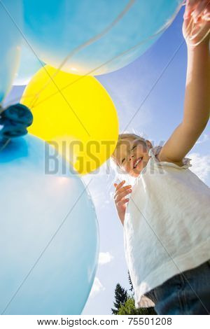 Low angle view of happy girl holding helium balloons against sky