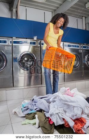 Happy young African American woman holding empty basket with clothes on floor at laundry
