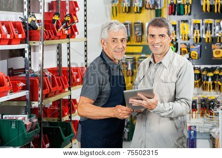 Portrait of salesman and customer using tablet computer in hardware store