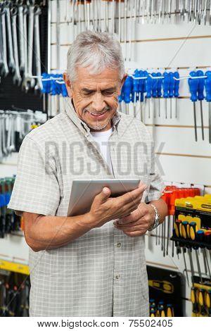 Smiling senior customer using digital tablet while standing in hardware shop