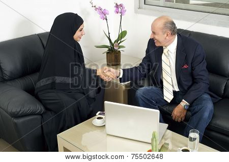 Senior Businessman Shaking hands with Woman wearing hijab, Multiracial Businesspeople shaking hands
