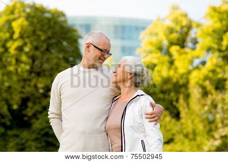 family, age, tourism, travel and people concept - senior couple hugging in city park