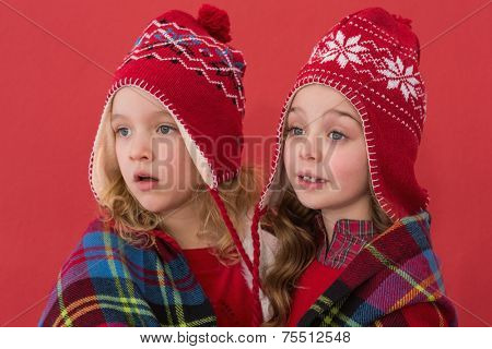 Festive little girls under a blanket on red background