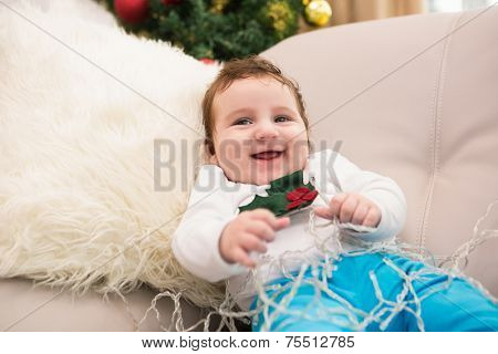 Cute baby boy on the couch at christmas at home in the living room