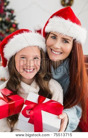Festive mother and daughter exchanging gifts at home in the living room