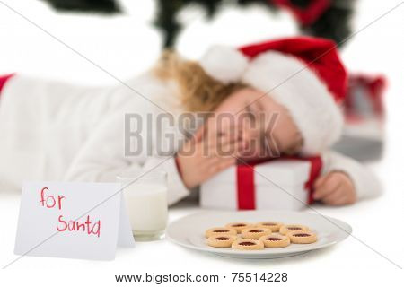Festive little girl napping on a gift on white background