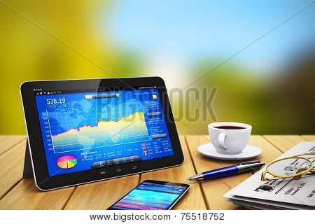 Tablet computer, smartphone and other business objects on wooden table outdoors
