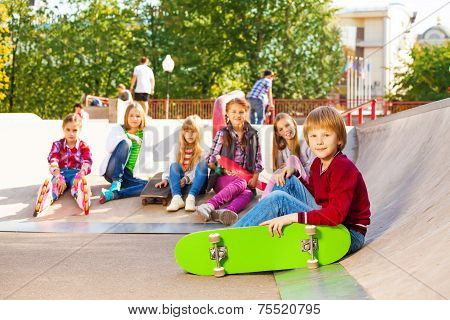 Blond boy with skateboard and his mates sit behind