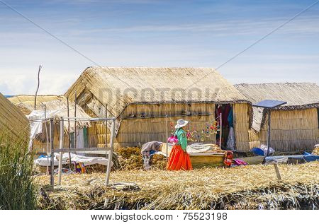 PUNO, PERU, MAY 5, 2014: Uros islands on Titicaca lake -  Local women in traditional attire pass by huts made from reed