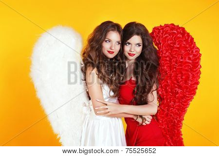 Happy Smiling Two Attractive Women Wearing In Angel Costume With Wing Isolated On Yellow Background.