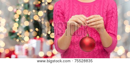 christmas, decoration, holidays and people concept - close up of woman in pink sweater holding christmas ball over tree lights background