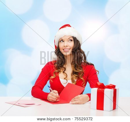 christmas, holidays, celebration, greeting and people concept - smiling woman in santa helper hat with gift box writing letter or sending post card over blue lights background