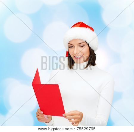 christmas, holidays, celebration, greeting and people concept - smiling woman in santa helper hat with greeting card over blue lights background