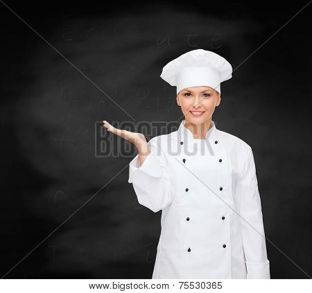 cooking, advertisement and people concept - smiling female chef, cook or baker holding something on palm of hand over blackboard background
