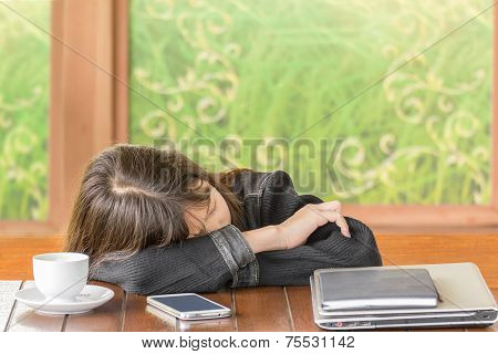 Asian Girl Sleeping While Sitting At Desk