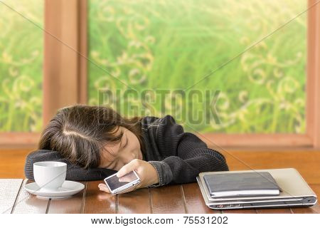 Asian Girl Sleeping And Hold Smartphone In Hand