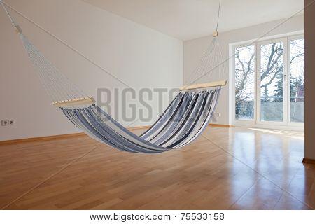 Comfortable hammock hanging in an empty room (3D Rendering)