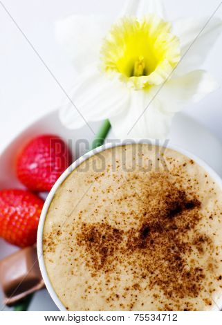 Coffee mocha with strawberries, chocolate and flower as garnish.